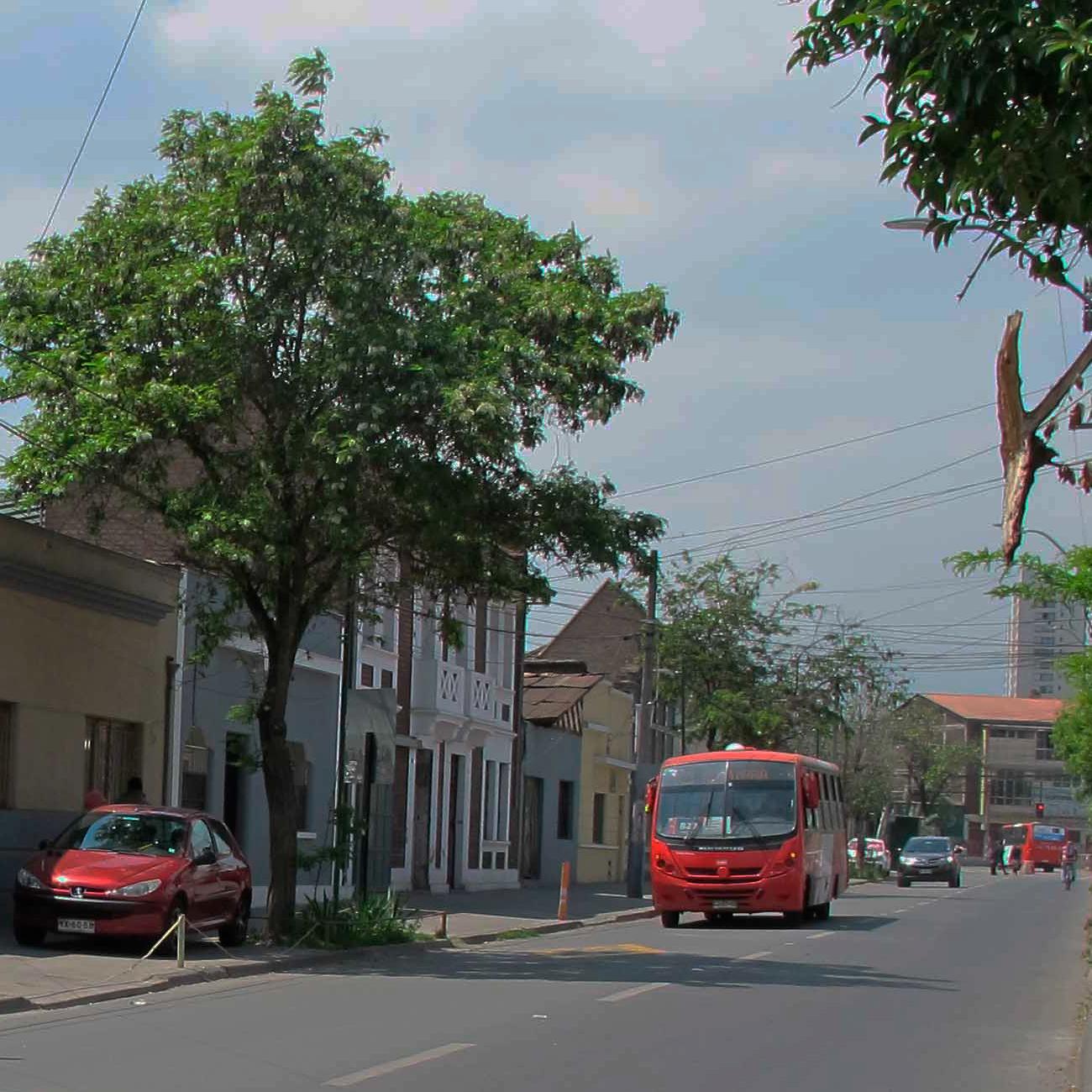 calle de ciudad con bus y con auto estacionado en la vereda